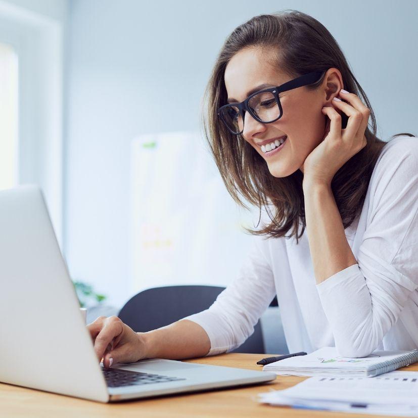 Jeune femme assise à son bureau souriante