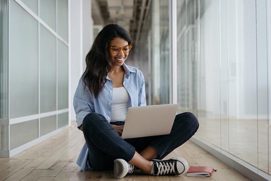 Femme noire assise avec son ordinateur sur les genoux