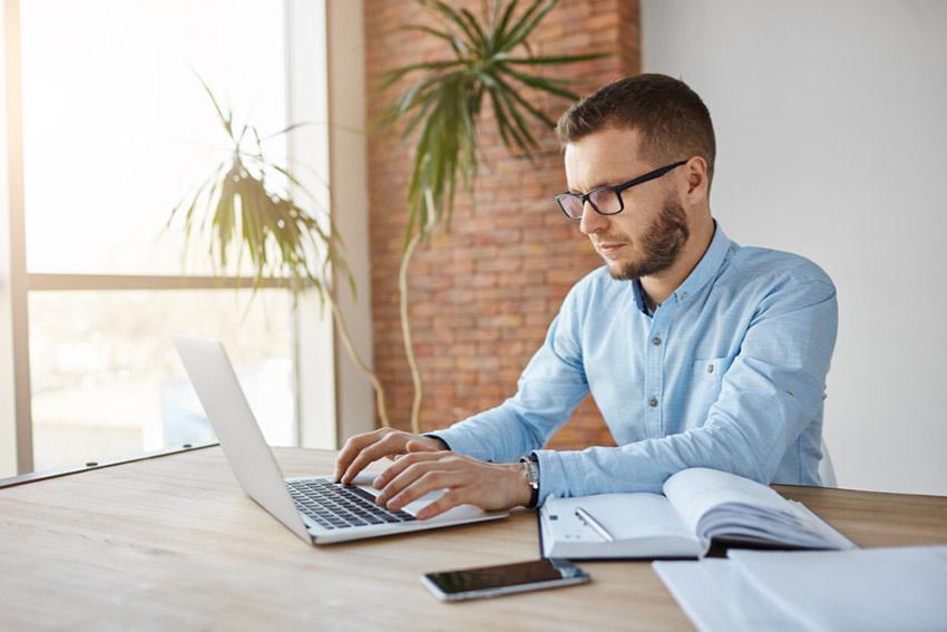 Jeune homme à lunettes Freelance devant son ordinateur